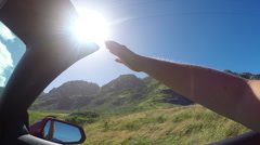 SLOW MOTION: Arm outside of convertible car playing with wind against sunny sky - stock footage