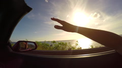 SLOW MOTION: Driving along the beach at sunrise hand waving in the summer wind - stock footage