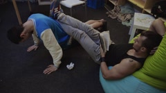 Muscle man read book on beanbag, keep legs on boy in sport jacket press up from - stock footage