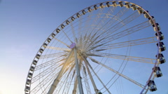Majestic observation wheel rotating in amusement park, sunny blue sky background Stock Footage