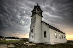 Storm Clouds Saskatchewan with old wooden church in foreground Stock Photos