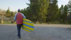 Camera tracks guy holding surf board Stock Footage