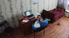 Young boy sitting at notebook in dormitory room and drink milk from bottle, eat Stock Footage