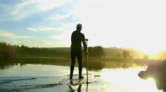 Guy paddle boards away into distance Stock Footage