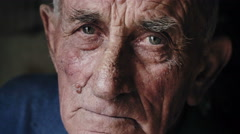 Blue eyes old man looks to the camera - stock footage