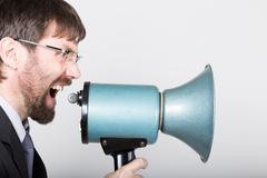 bearded businessman yelling through bullhorn. Public Relations. man expresses - stock photo