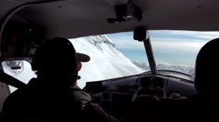 Bush Pilot and Copilot Flying Past Steep Alpine Slope in Alaska Stock Footage
