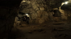 A young man is standing inside a rock cave - stock footage