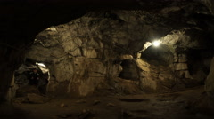 A young man is standing inside a rock cave Stock Footage
