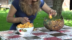 Peasant girl clean chanterelle mushrooms on table. 4K Stock Footage
