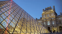 Louvre Pyramid glass construction brightly illuminated by lights at night, Paris - stock footage
