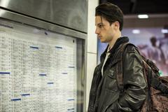 Young man traveling, reading train timetable in railway station Kuvituskuvat