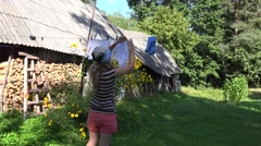 Poor country woman girl hanging laundry towel on clothesline string in rural Stock Footage