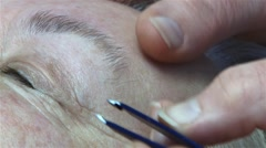 Hands of beautician pluck with tweeze hairs from the eyebrows his client, who Stock Footage
