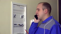 Stressed amateur electrician guy consulting with colleague on smart phone Stock Footage