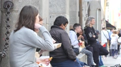 Girls sit rest eating fast food hamburger and snacks on public place in Milan Stock Footage
