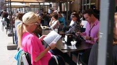 People rest sit eat and drink in a restaurant in city center square in Milan  Stock Footage