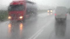 Windshield wiper sweeping water while the car is moving with speed on a road - stock footage