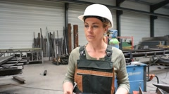 Woman in metal factory checking instructions with tablet - stock footage