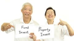 Happy Asian senior couple with sign fund and property investment concept - stock photo