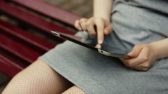 Woman working on tablet computer sitting on bench outdoors. Close up Stock Footage