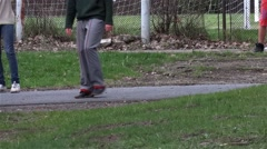 Group of youths playing football in the park on a driveway, where passing cyclis Stock Footage