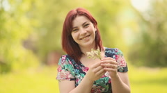 A young woman hesitates. Holding a bouquet of flowers Stock Footage