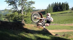 Motorcyclists that their motocross climb a small ravine in the fir forest - stock footage