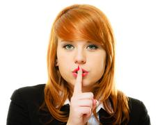 Girl with  finger on lips hush hand gesture - stock photo