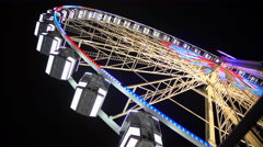 Giant wheel starts rotating and gaining speed, bright illumination sparkling Stock Footage