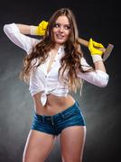 Sexy alluring woman holding hammer. Feminism. Stock Photos