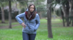 Young lady walks in a park talking with earphone Stock Footage
