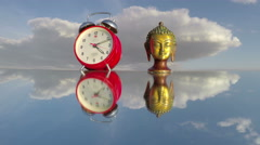 Buddha head sculpture and red clock on mirror, time lapse 4K Stock Footage