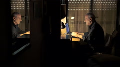 Elder man chatting with the computer in his room's twilight Stock Footage