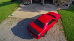 Red Dodge Challenger sports car backing up and turning around to leave - stock footage