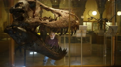 4KMother & son in natural history museum looking through glass at dinosaur skull Stock Footage