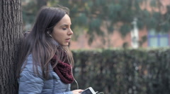 Profile of smiling woman in the park speaking with earphone Stock Footage
