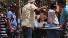 Elderly man preparing snow cones for people waiting at a food drive in Panama Stock Footage