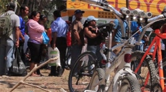 Bikes parked next to a large line at a food drive in Panama Stock Footage
