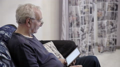 Pensioner sit on the sofa while using tablet - stock footage