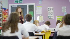 4K Young students listening to teacher & asking questions in school classroom. - stock footage