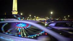 Cars driving by Obelisk of Luxor in Paris, Eiffel Tower sparkling at night Stock Footage