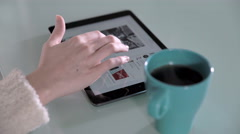 Young woman's hand using tablet during breakfast Stock Footage