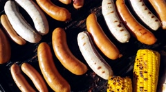 Grilling sausages, bratwursts, corn and chicken, on a gas barbeque Stock Footage