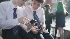4K School boys looking at mobile phones outdoors in school playground. - stock footage