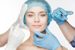 Attractive woman at plastic surgery with syringe in her face Stock Photos