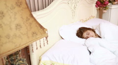A beautiful young woman lying in bed comfortably and blissfully. luxury interior Stock Footage