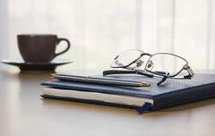 Pen and Glasses on a book - stock photo