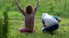 Two kids have fun on green grass, sing and laugh, back to camera - stock footage