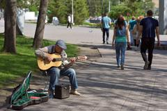 NOVOSIBIRSK/RUSSIA-MAY 22, 2016: Elderly musician playing guitar in city park Stock Photos